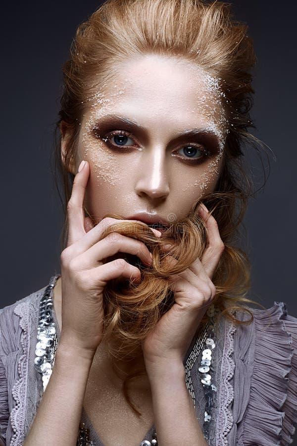 Νέο κορίτσι με το δημιουργικές makeup και τις συστάσεις στο πρόσωπό της Όμορφο πρότυπο σε ένα ιώδες φόρεμα με τα σπινθηρίσματα στοκ εικόνες