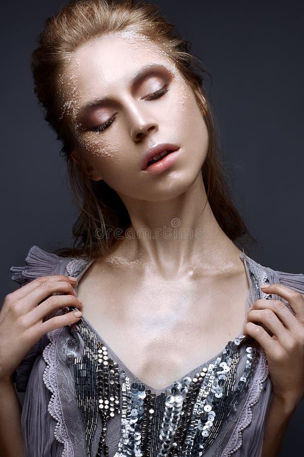 Νέο κορίτσι με το δημιουργικές makeup και τις συστάσεις στο πρόσωπό της Όμορφο πρότυπο σε ένα ιώδες φόρεμα με τα σπινθηρίσματα στοκ εικόνα με δικαίωμα ελεύθερης χρήσης