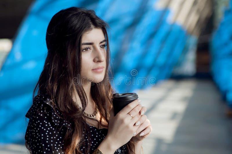 Νέο κορίτσι με το μακρυμάλλη καφέ σκέψης και κατανάλωσης στην αστική οδό πόλεων Σοβαρή γυναίκα με το μίας χρήσης φλυτζάνι στοκ φωτογραφία με δικαίωμα ελεύθερης χρήσης
