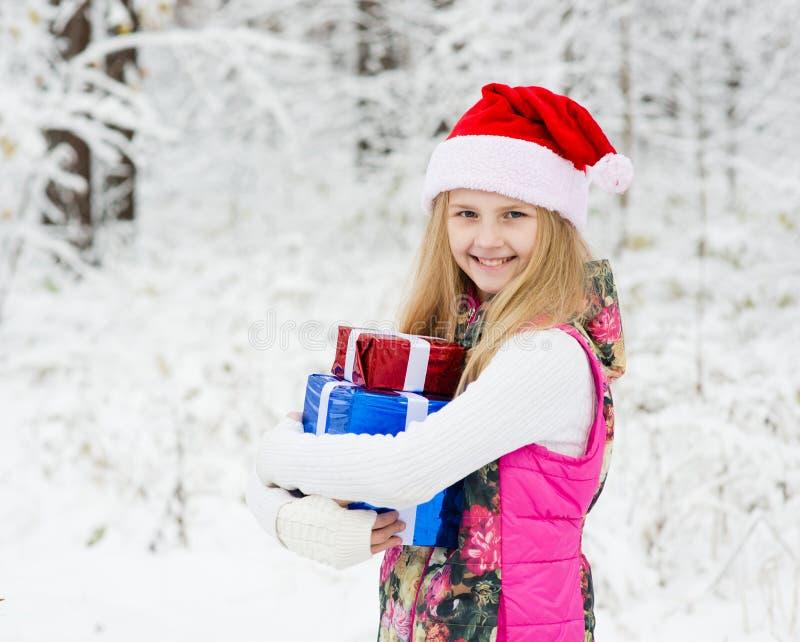 Νέο κορίτσι με το σωρό εκμετάλλευσης καπέλων santa των δώρων στοκ φωτογραφία με δικαίωμα ελεύθερης χρήσης