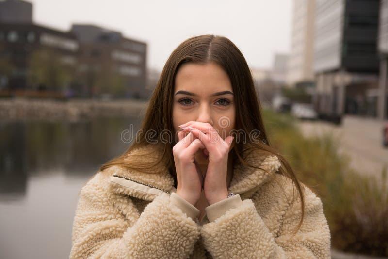Νέο κορίτσι με το χειμερινό παλτό στην πόλη στοκ φωτογραφίες