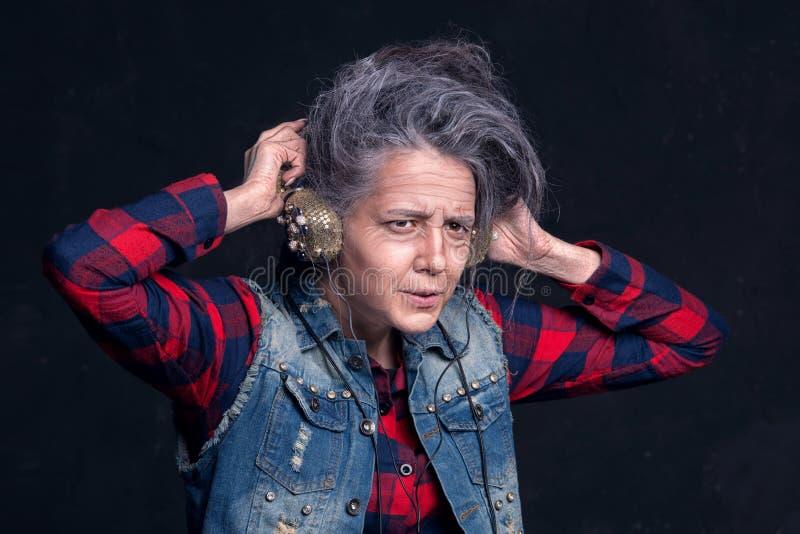 Νέο κορίτσι με το makeup της ανώτερης γυναίκας Η ηλικιωμένη γιαγιά ακούει τη μουσική στα ακουστικά στοκ φωτογραφία