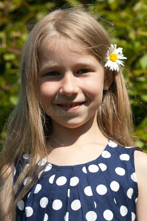 Νέο κορίτσι με camomile το λουλούδι στην τρίχα στοκ εικόνα