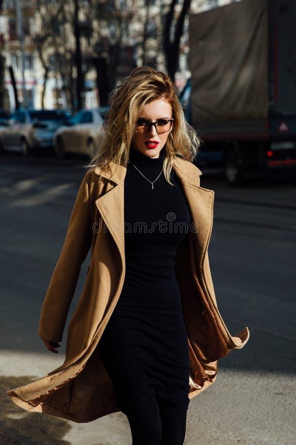 Νέο κορίτσι μόδας στα γυαλιά Ξανθά, κόκκινα χείλια, μπεζ παλτό που περπατούν κατά μήκος της οδού πόλεων στοκ εικόνες