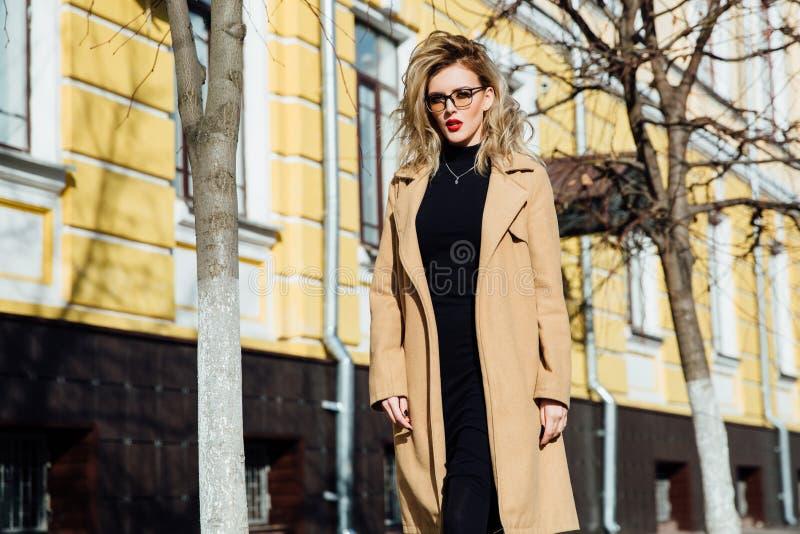 Νέο κορίτσι μόδας στα γυαλιά Ξανθά, κόκκινα χείλια, μπεζ παλτό που περπατούν κατά μήκος της οδού πόλεων στοκ φωτογραφία με δικαίωμα ελεύθερης χρήσης