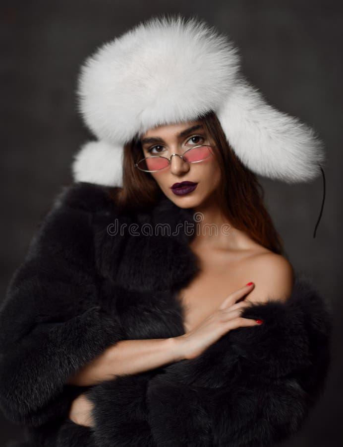 Νέο κορίτσι μόδας στο παλτό γουνών και λευκό καπέλο στα σύγχρονα ρόδινα γυαλιά ηλίου στο σκοτάδι στοκ φωτογραφία με δικαίωμα ελεύθερης χρήσης