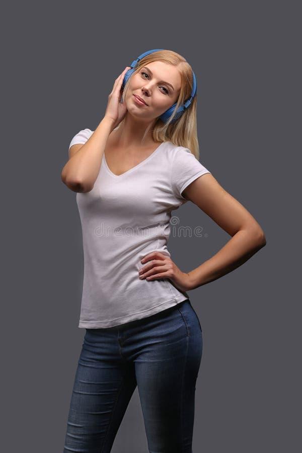 Νέο κορίτσι ξανθό στα μπλε ακουστικά Άκουσμα, που απολαμβάνει τη μουσική Απομονώστε σε ένα γκρίζο υπόβαθρο στοκ φωτογραφίες με δικαίωμα ελεύθερης χρήσης