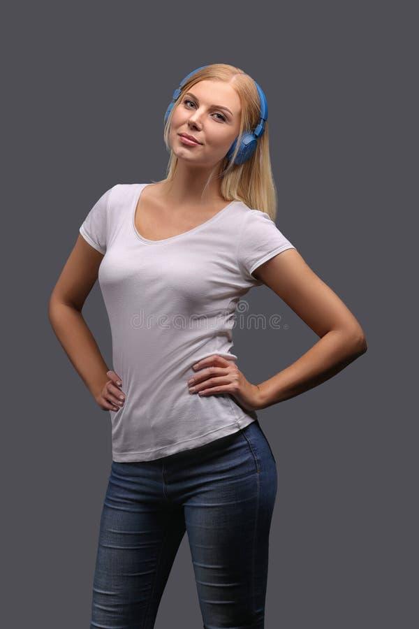 Νέο κορίτσι ξανθό στα μπλε ακουστικά Άκουσμα, που απολαμβάνει τη μουσική Απομονώστε σε ένα γκρίζο υπόβαθρο στοκ εικόνα με δικαίωμα ελεύθερης χρήσης