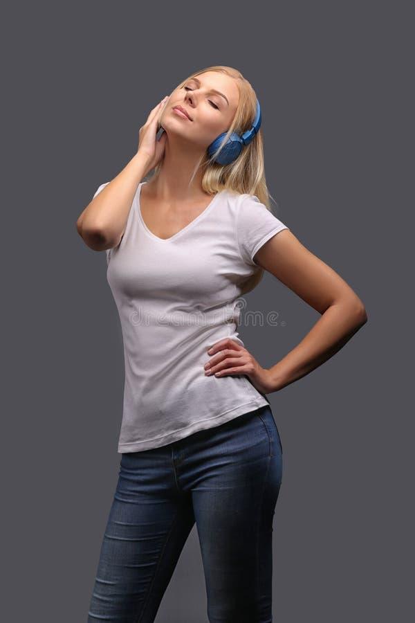 Νέο κορίτσι ξανθό στα μπλε ακουστικά Άκουσμα, που απολαμβάνει τη μουσική Απομονώστε σε ένα γκρίζο υπόβαθρο στοκ φωτογραφίες