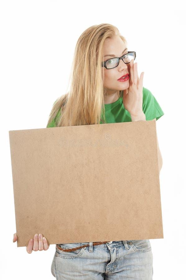 Νέο κορίτσι ομορφιάς που κρατά τον κενό ξύλινο πίνακα και τη φθορά ανακοινώσεων στοκ εικόνες