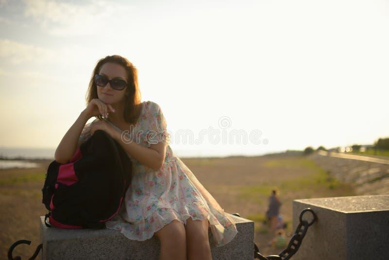 Νέο κορίτσι ο ταξιδιώτης σε ένα φόρεμα και ένα σακίδιο πλάτης στοκ εικόνες