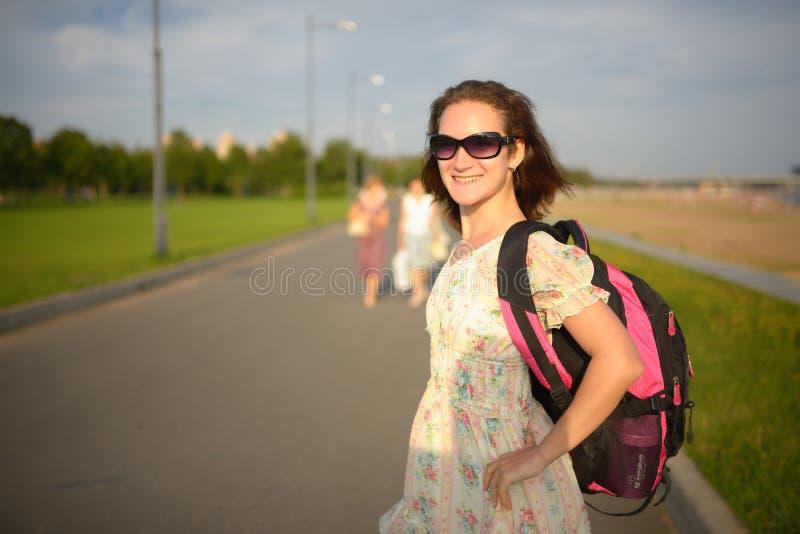Νέο κορίτσι ο ταξιδιώτης σε ένα φόρεμα και ένα σακίδιο πλάτης στοκ φωτογραφία με δικαίωμα ελεύθερης χρήσης