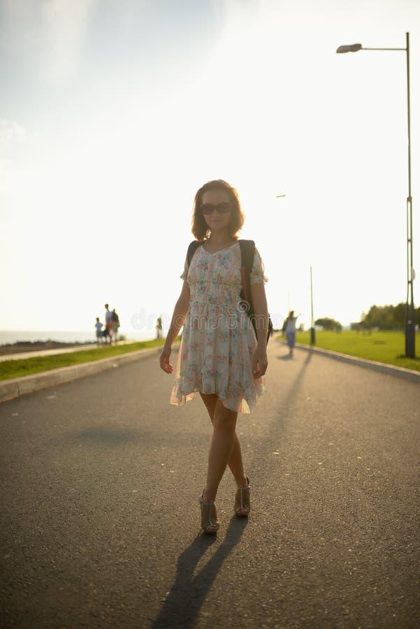 Νέο κορίτσι ο ταξιδιώτης σε ένα φόρεμα και ένα σακίδιο πλάτης στοκ εικόνα με δικαίωμα ελεύθερης χρήσης