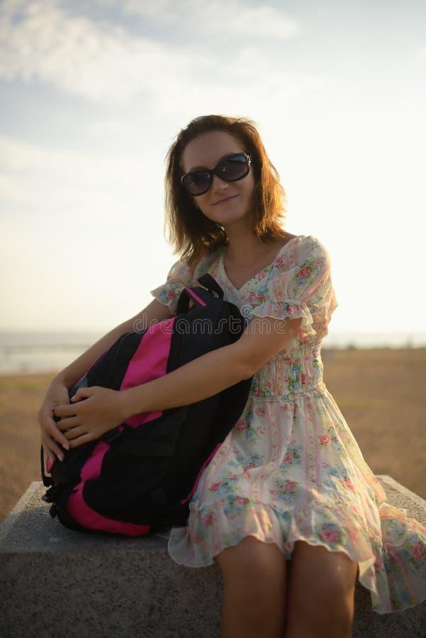 Νέο κορίτσι ο ταξιδιώτης σε ένα φόρεμα και ένα σακίδιο πλάτης στοκ φωτογραφία
