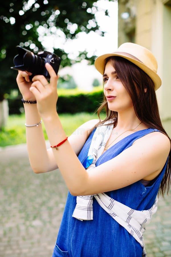 Νέο κορίτσι που έχει τη διασκέδαση στην πόλη με τη φωτογραφία ταξιδιού καμερών του φωτογράφου που κάνει τις εικόνες στοκ φωτογραφία με δικαίωμα ελεύθερης χρήσης
