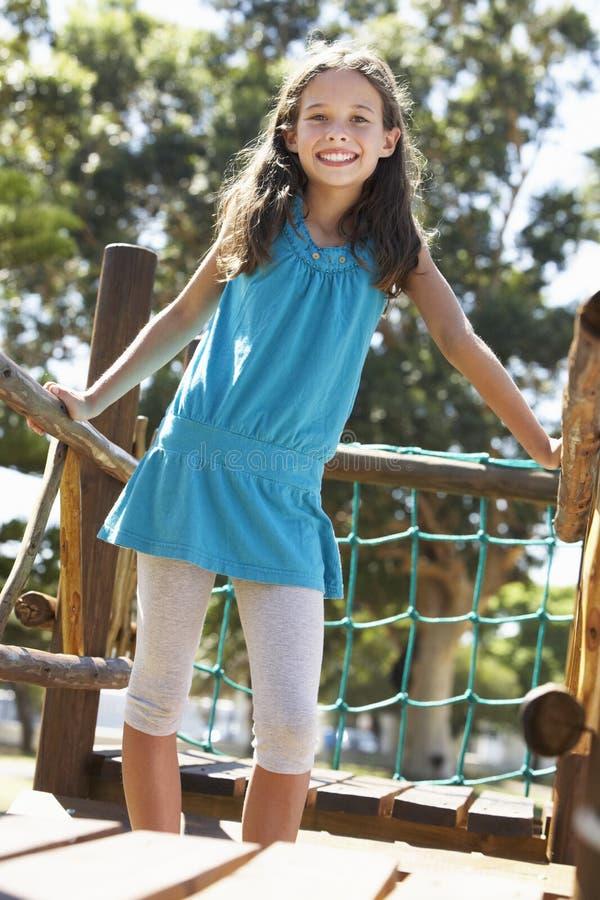 Νέο κορίτσι που έχει τη διασκέδαση στο πλαίσιο αναρρίχησης στοκ εικόνα