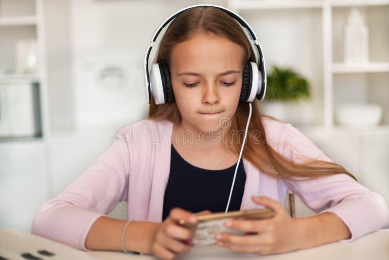 Νέο κορίτσι που ακούει τη μουσική στο τηλέφωνο και την κάσκα της στοκ εικόνες