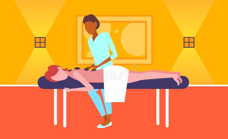 Νέο κορίτσι που απολαμβάνει την παραδοσιακή καυτή μασέρ αφροαμερικάνων μασάζ πετρών που τρίβει υπομονετική woman hotel health spa ελεύθερη απεικόνιση δικαιώματος
