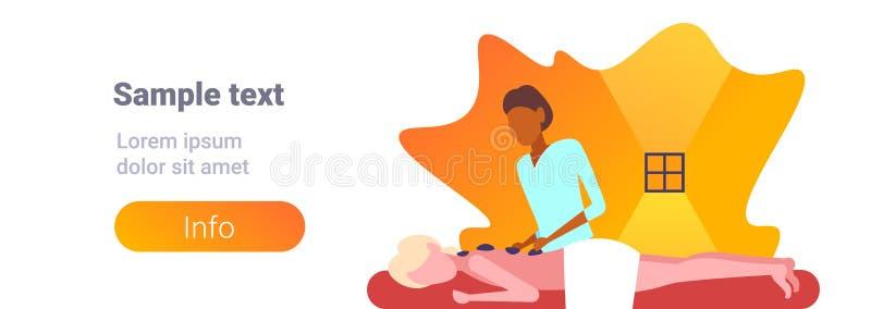 Νέο κορίτσι που απολαμβάνει την παραδοσιακή καυτή μασέρ αφροαμερικάνων μασάζ πετρών που τρίβει υπομονετική woman hotel health spa απεικόνιση αποθεμάτων