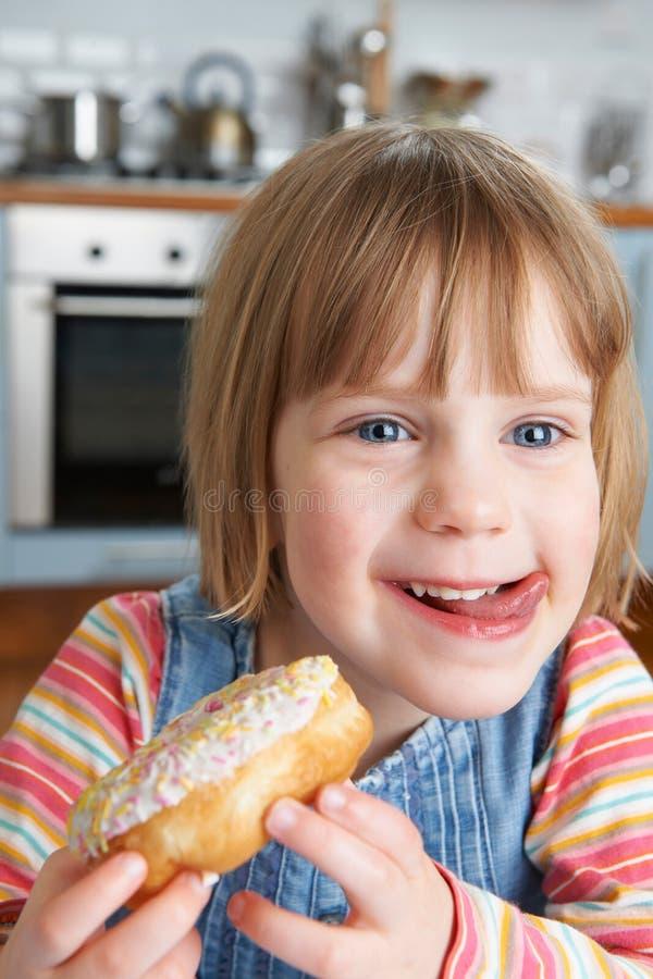 Νέο κορίτσι που απολαμβάνει κολλώδες Doughnut στοκ εικόνα