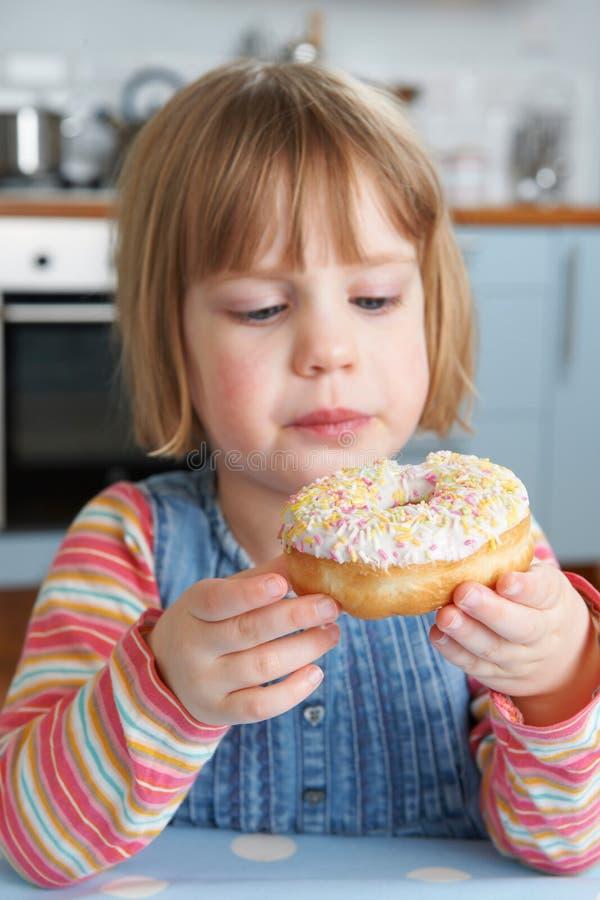 Νέο κορίτσι που απολαμβάνει τρώγοντας ζαχαρούχο Doughnut στοκ φωτογραφία με δικαίωμα ελεύθερης χρήσης