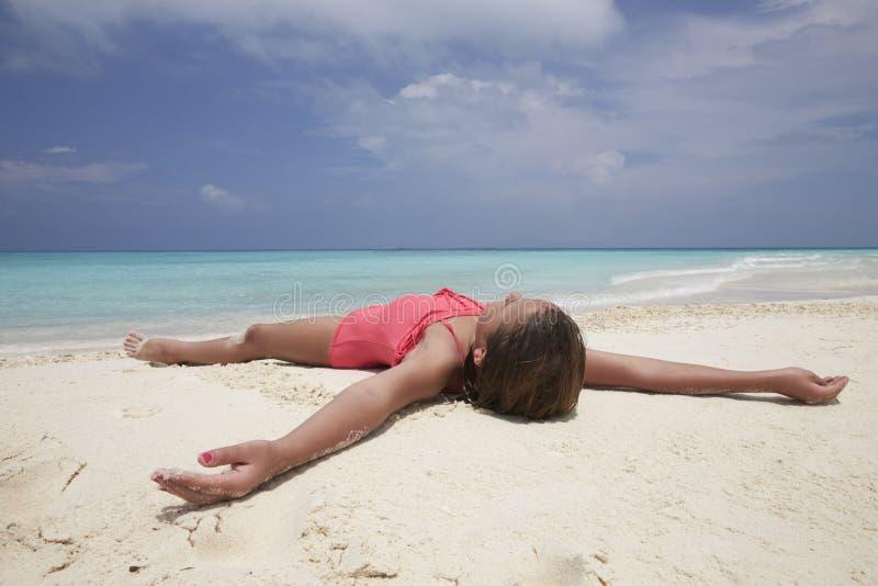 Νέο κορίτσι που βρίσκεται σε μια άσπρη παραλία άμμου από τον ωκεανό στοκ εικόνα