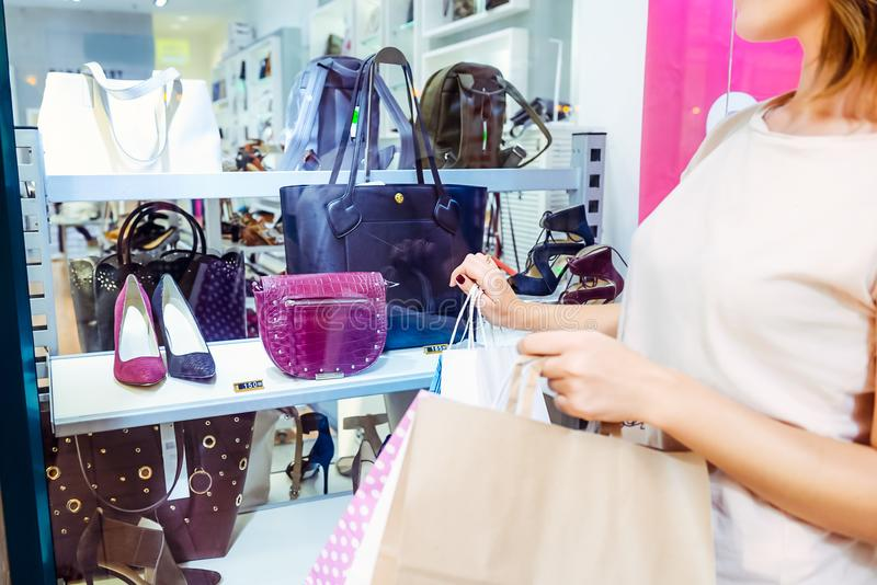 Νέο κορίτσι που εξετάζει την προθήκη με τα παπούτσια και τις τσάντες στη λεωφόρο αγορών Αγοραστής πωλήσεις αγορές κεντρικών εσωτε στοκ φωτογραφίες