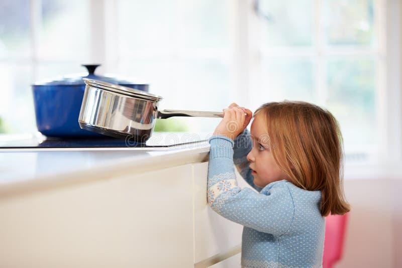 Νέο κορίτσι που διακινδυνεύει το ατύχημα με το τηγάνι στην κουζίνα στοκ εικόνες