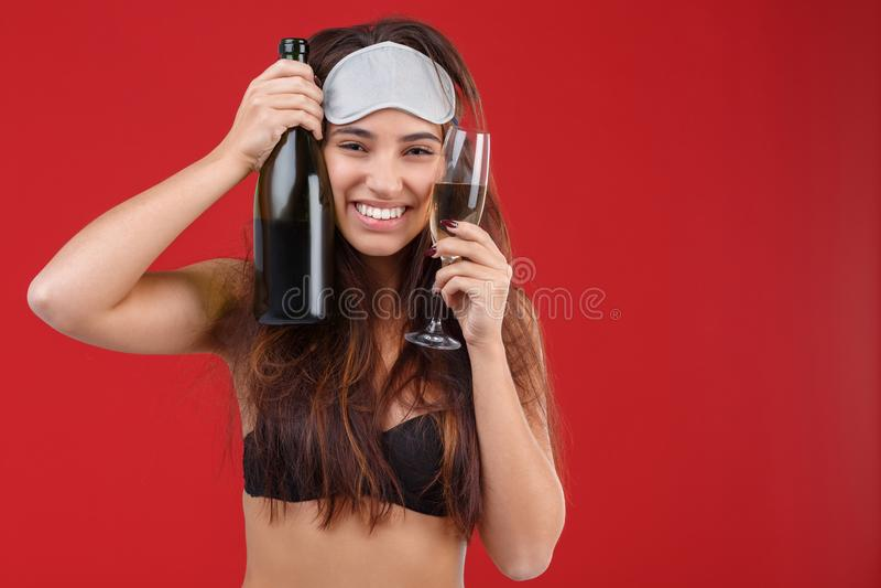 Νέο κορίτσι που κρατά ένα μπουκάλι και ένα ποτήρι της σαμπάνιας στοκ εικόνες