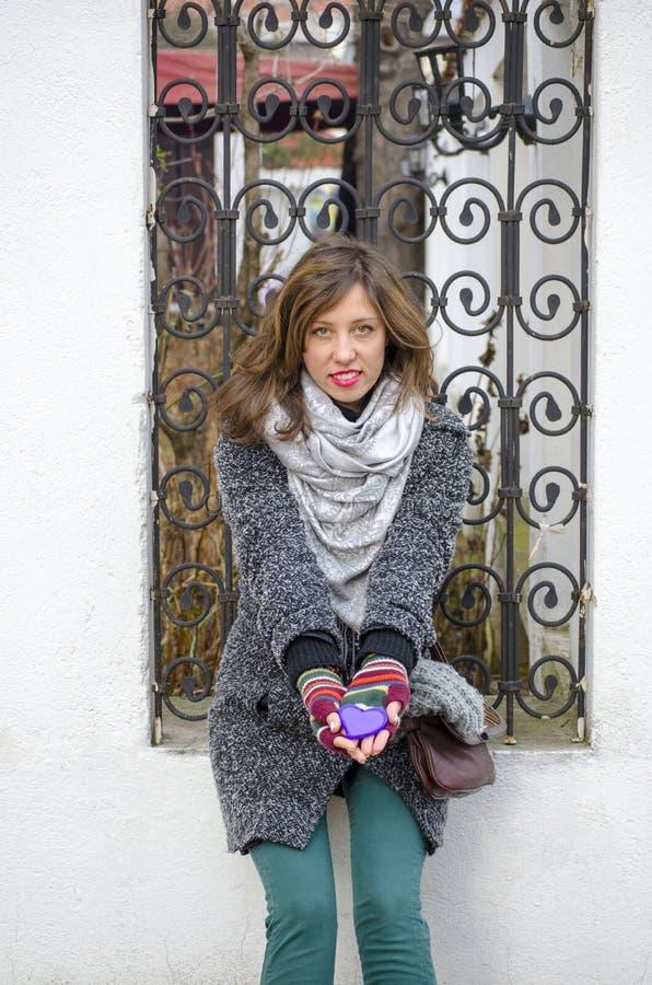 Νέο κορίτσι που κρατά μια πορφυρή καρδιά υπαίθρια στοκ φωτογραφίες