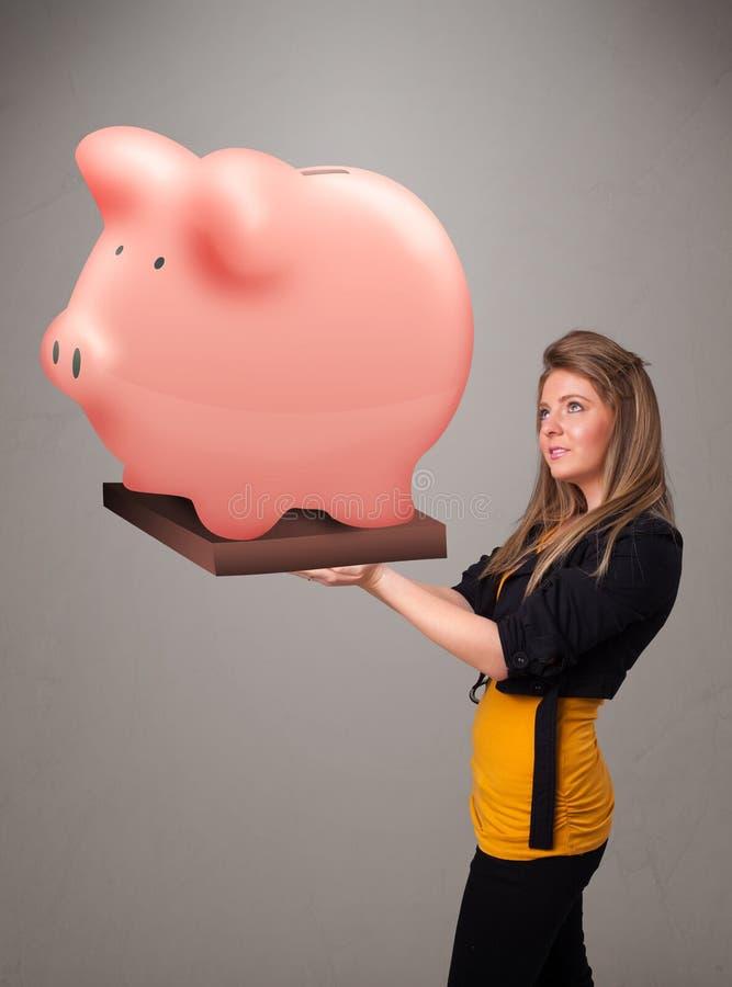 Νέο κορίτσι που κρατά μια τεράστια piggy τράπεζα αποταμίευσης απεικόνιση αποθεμάτων