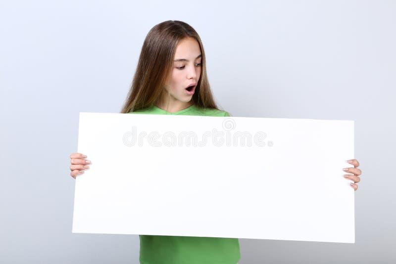 Νέο κορίτσι που κρατά τον κενό πίνακα στοκ φωτογραφίες
