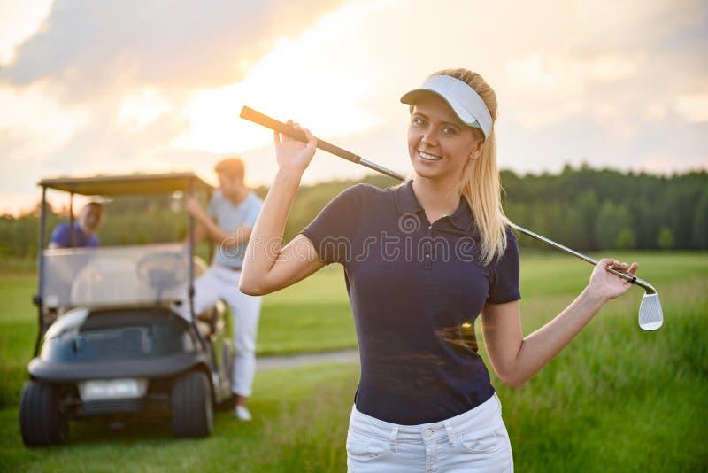 Νέο κορίτσι που κρατά το γκολφ κλαμπ της στοκ εικόνες