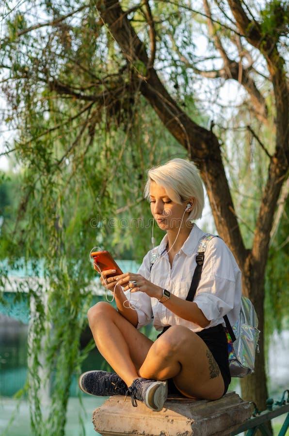Νέο κορίτσι που κρατά το τηλέφωνό της και που ακούει τη μουσική στοκ φωτογραφία με δικαίωμα ελεύθερης χρήσης