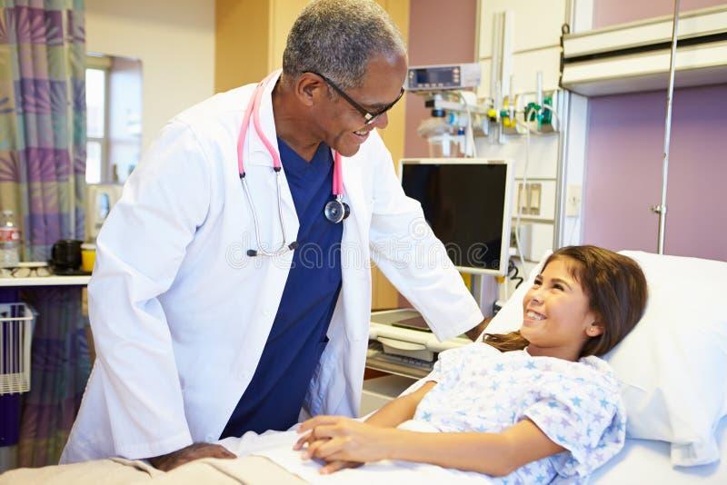 Νέο κορίτσι που μιλά στον αρσενικό γιατρό στο δωμάτιο νοσοκομείων στοκ εικόνα με δικαίωμα ελεύθερης χρήσης