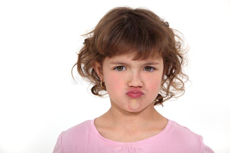 Νέο κορίτσι που παρεκκλίνει το πρόσωπό της στοκ εικόνα