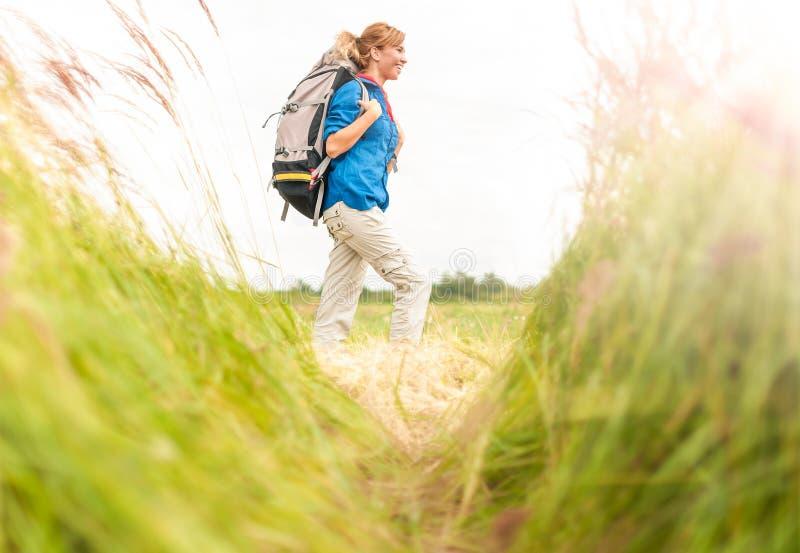 Νέο κορίτσι που περπατά στο λιβάδι με backpack επάνω. στοκ εικόνες