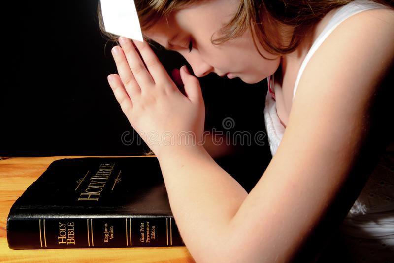 Νέο κορίτσι που προσεύχεται πέρα από τη Βίβλο στοκ φωτογραφία με δικαίωμα ελεύθερης χρήσης
