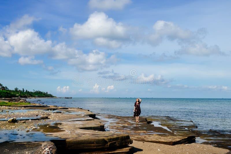 Νέο κορίτσι που στέκεται στους ηφαιστειακούς βράχους στο νησί στοκ εικόνα