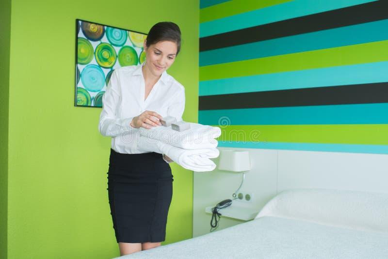 Νέο κορίτσι που τακτοποιεί το κρεβάτι στο δωμάτιο ξενοδοχείου στοκ φωτογραφία με δικαίωμα ελεύθερης χρήσης