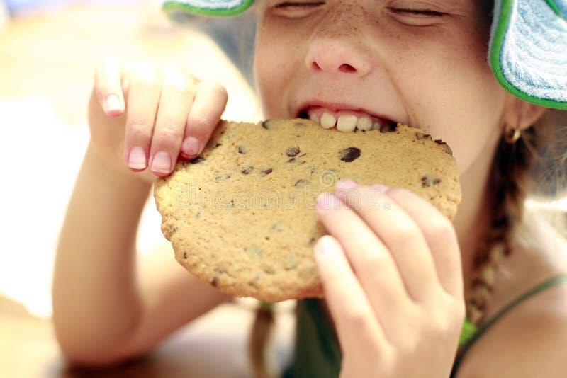 Νέο κορίτσι που τρώει ένα μεγάλο μπισκότο στοκ εικόνες