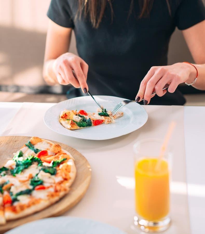 Νέο κορίτσι που τρώει την πίτσα σε ένα εστιατόριο στοκ εικόνες