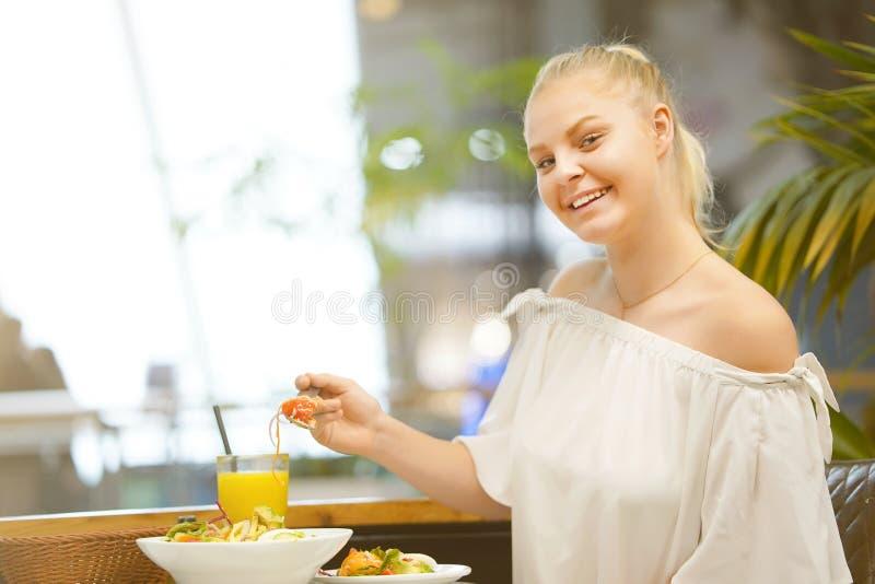 Νέο κορίτσι που τρώει τη σαλάτα σε έναν καφέ στοκ φωτογραφίες