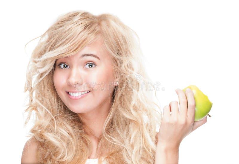 Νέο κορίτσι που τρώει το πράσινο μήλο στην άσπρη ανασκόπηση. στοκ εικόνα