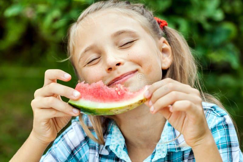 Νέο κορίτσι που τρώει το ώριμο καρπούζι στοκ φωτογραφίες