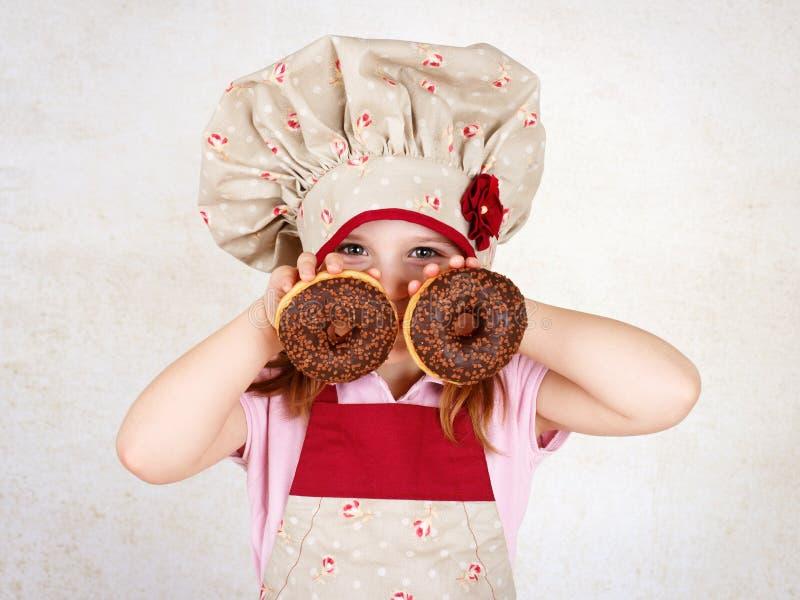 Νέο κορίτσι που τρώει donuts στοκ εικόνες