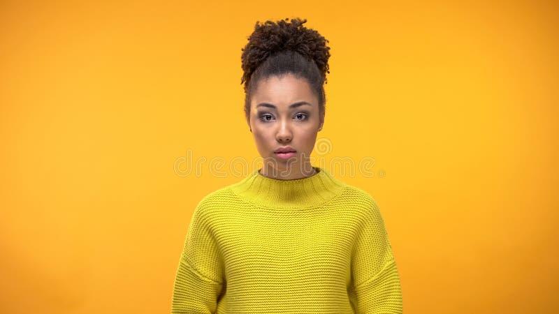 Νέο κορίτσι που φαίνεται κεκλεισμένων των θυρών στο κίτρινο υπόβαθρο,  στοκ φωτογραφία
