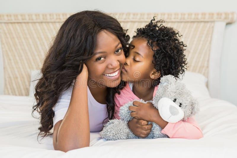 Νέο κορίτσι που φιλά τη χαμογελώντας μητέρα της στο κρεβάτι στοκ εικόνες