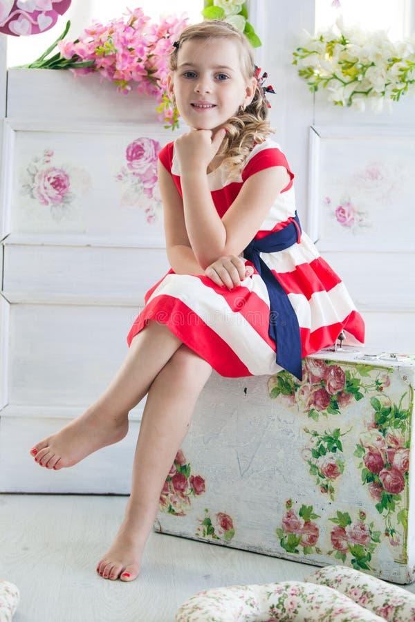 Νέο κορίτσι που φορά ένα φόρεμα με την εκλεκτής ποιότητας βαλίτσα στοκ φωτογραφίες
