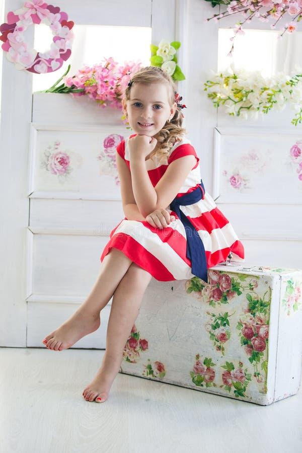 Νέο κορίτσι που φορά ένα φόρεμα με την εκλεκτής ποιότητας βαλίτσα στοκ εικόνα